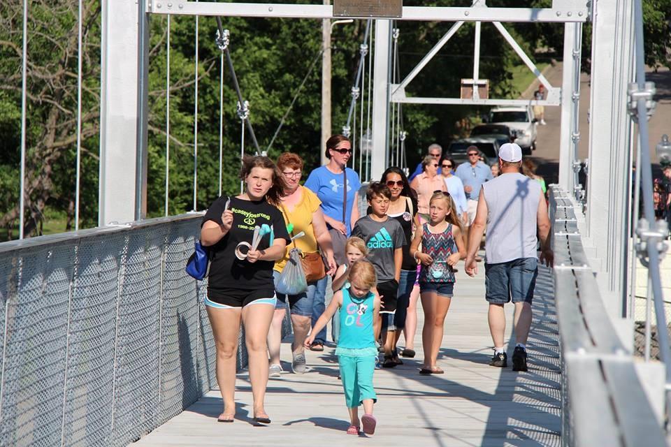 A lot of people walking across a pedestrian bridge on a sunny day.